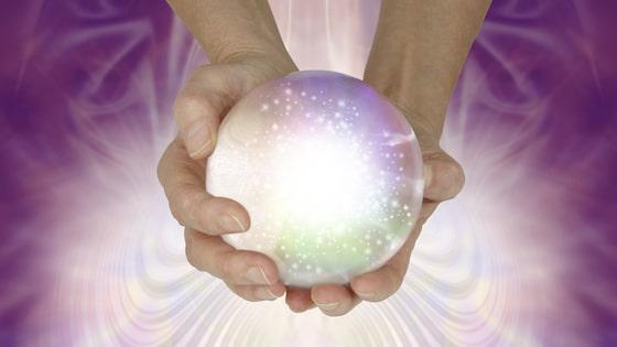 Mão segurando bola de cristal