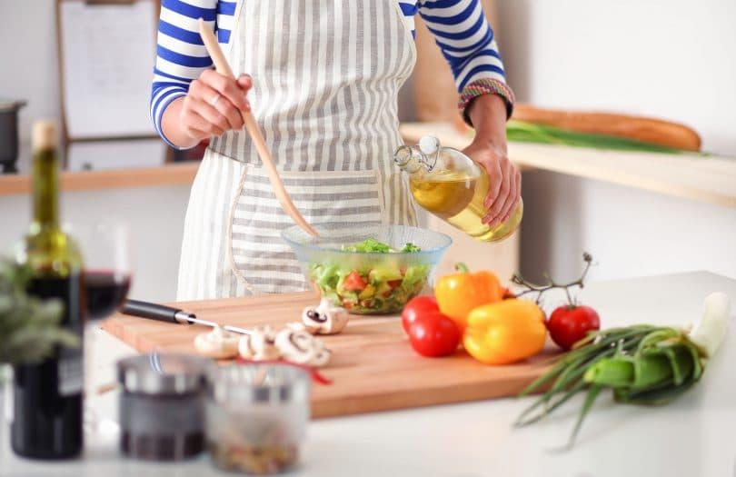 Mulher temperando salada de vegetais na cozinha.
