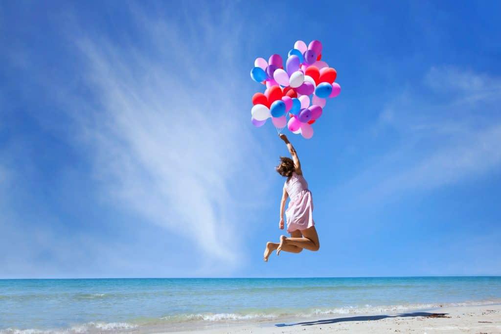 Mulher segurando balões e pulando na beira do mar.