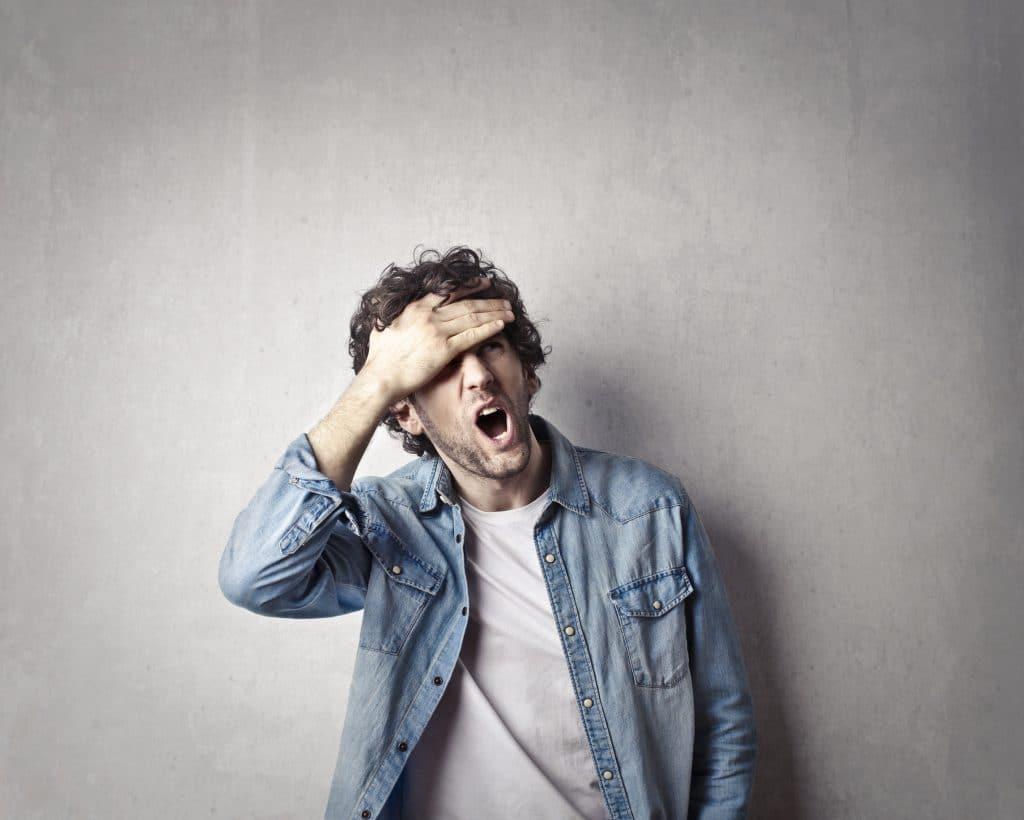 Homem gritando, com a mão na testa, encostado em uma parede cinza