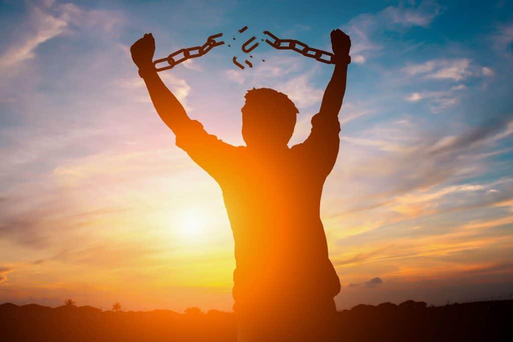 Silhueta de pessoa levantando os braço, quebrando uma corrente que prendia suas mãos, com pôr do sol ao fundo.