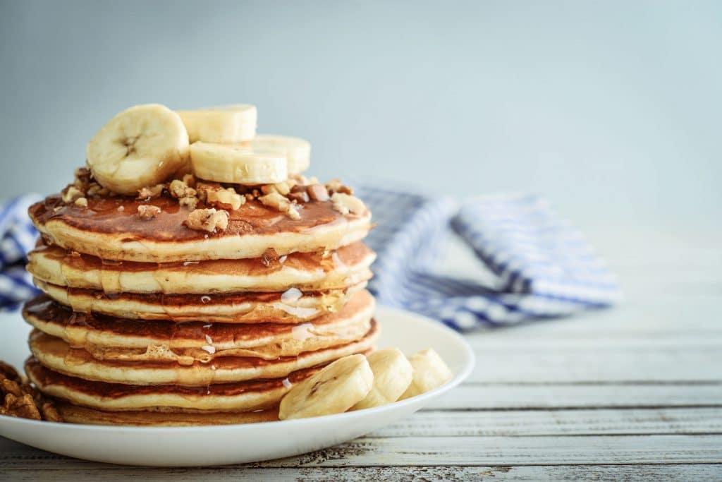 prato com panquecas americanas cobertas de melado e bananas fatiadas.