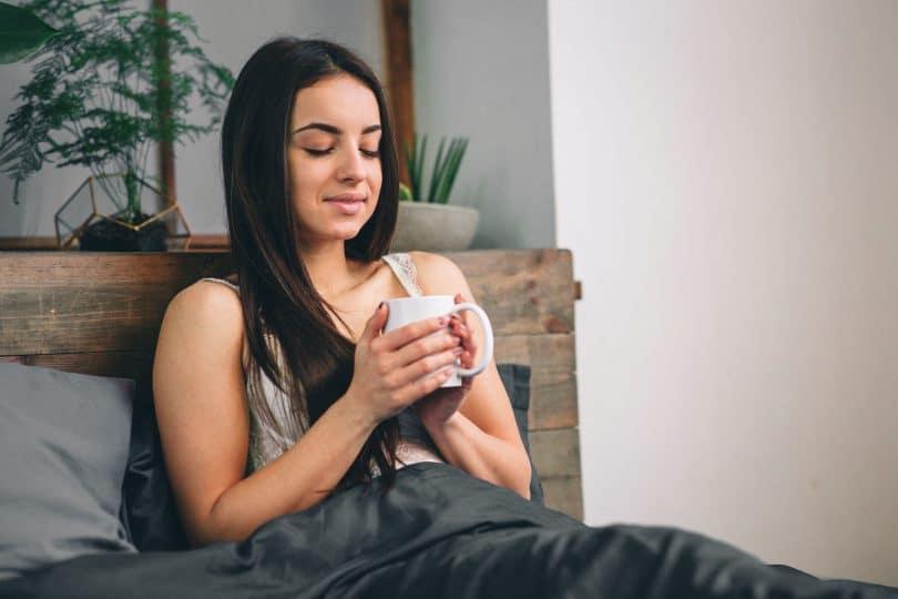 Mulher tomando chá de camomila enquanto está deitada na cama.
