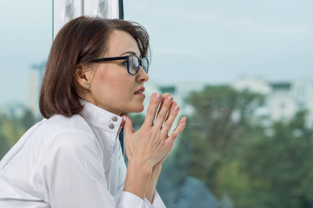 Mulher branca, com o cabelo curto e óculos de grau, olhando o horizonte apreensiva, com as mãos juntas em sinal de oração.
