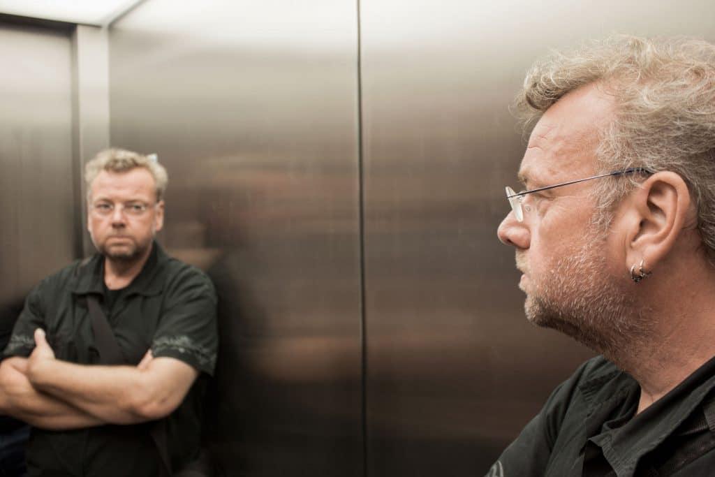 Homem branco, com cabelos grisalhos, vestindo camiseta preta e óculos de grau, se encarando de braços cruzados no espelho de um elevador.
