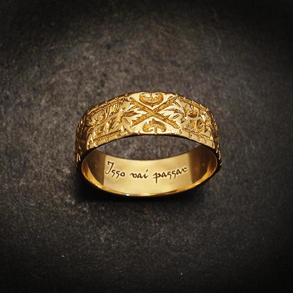 Anel de ouro, com escrito Isto também passará na parte interior, colocado em cima de mesa preta