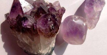 Três pedras de Ametista, uma grande natural e duas pequenas polidas, todas em cima de uma mesa branca.