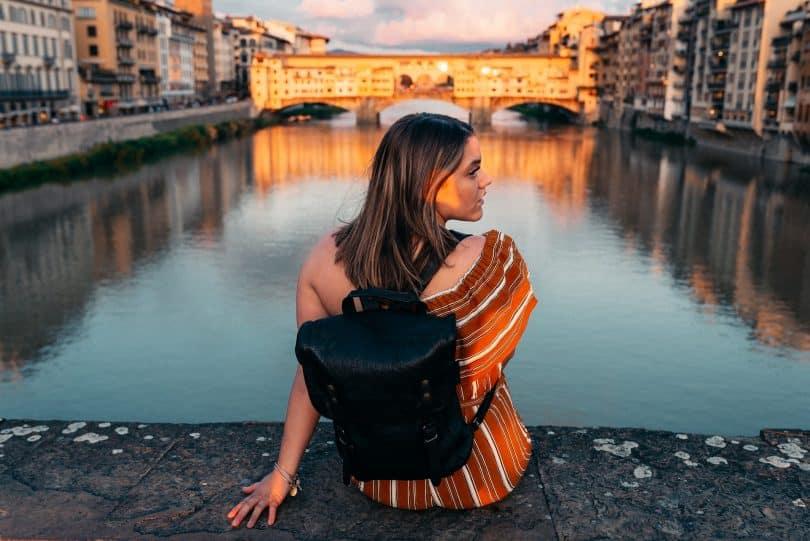 Mulher branca sentada na beira de rio.