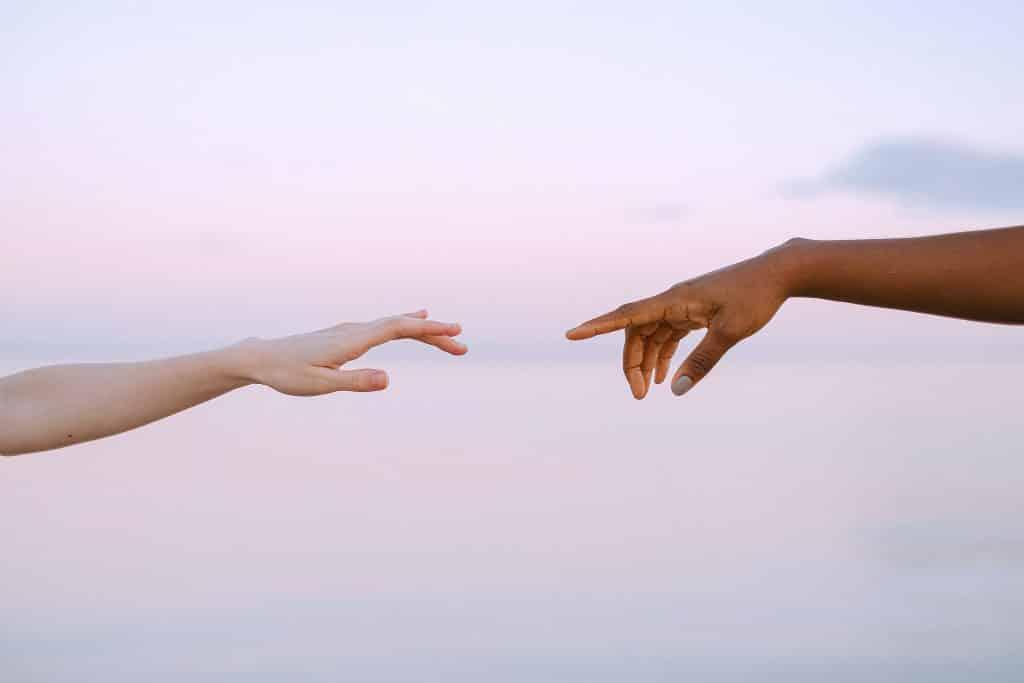 Mãos de duas pessoas e o céu de fundo