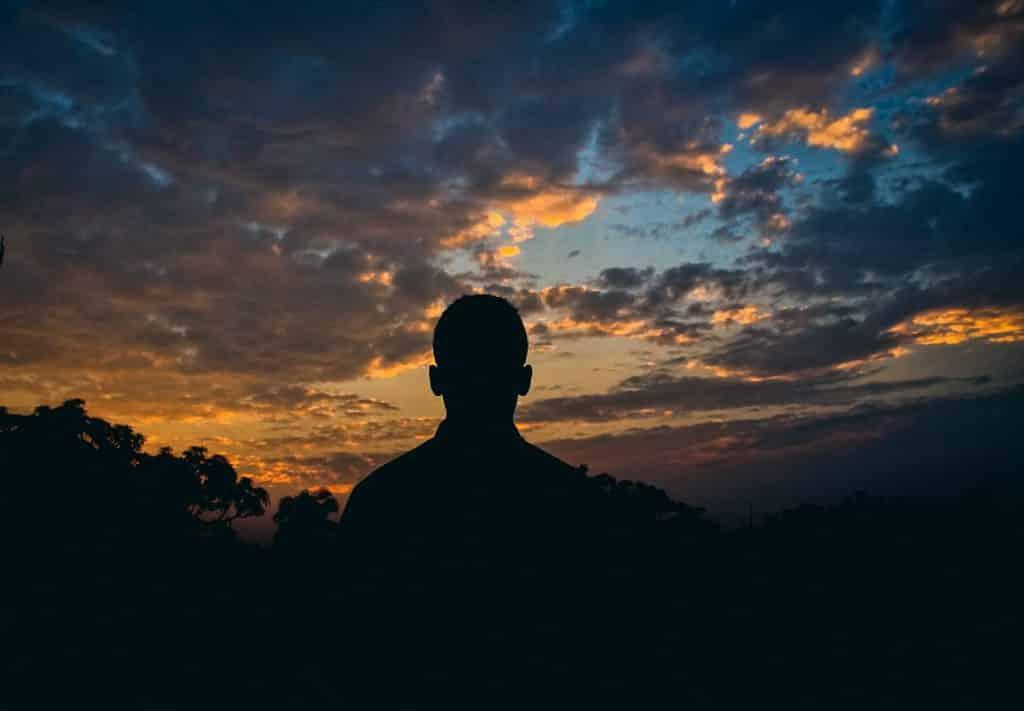 Homem olhando para o céu anoitecendo