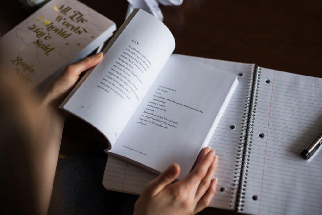 Livro aberto em cima de um caderno.