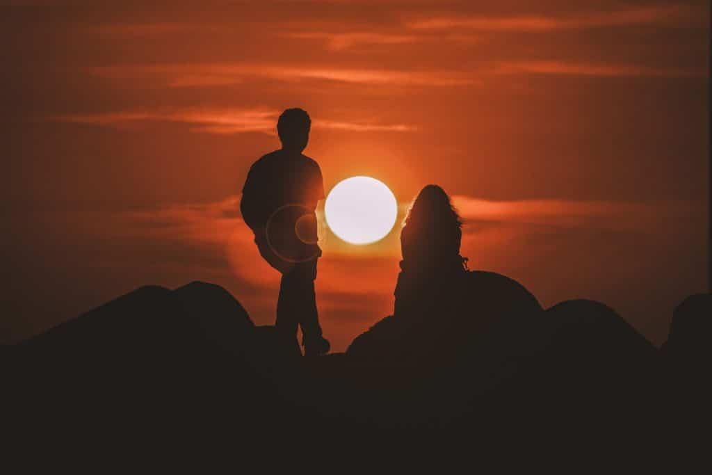 Silhueta de duas pessoas sentadas em uma montanha com o sol ao fundo.