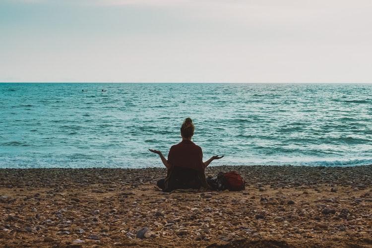 Mulher meditando em uma praia.