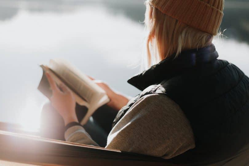 Mulher sentada em banco, observando a neve, com a bíblia em suas mãos, observando a paisagem.