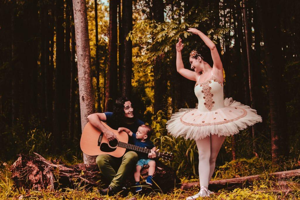 Mulher vestida de bailarina em pé. Um homem sentado em um tronco de arvore tocando violão. Ambos estão se olhando e sorrindo. Eles estão em uma floresta. Ser quando crescer.