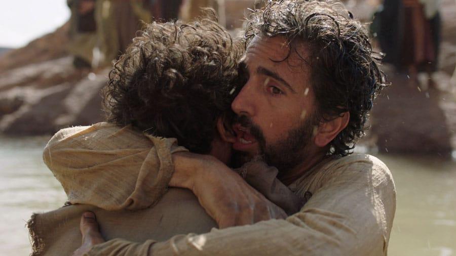 Imagem de jesus abraçando um outro homem no mar.
