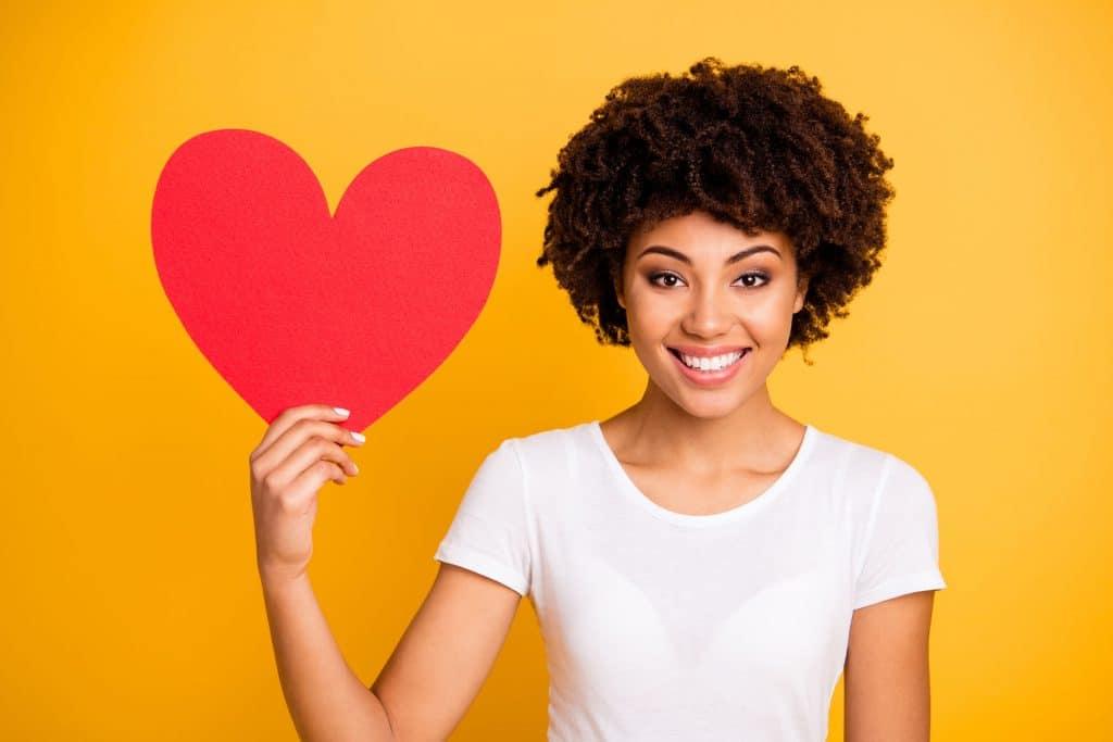 Mulher negra, jovem, vestindo uma camiseta branca, segurando um coração vermelho, feito de papel, em frente a uma parede laranja