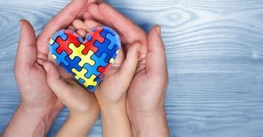 Mãos de criança e adulto brancas segurando coração de quebra-cabeça colorido.