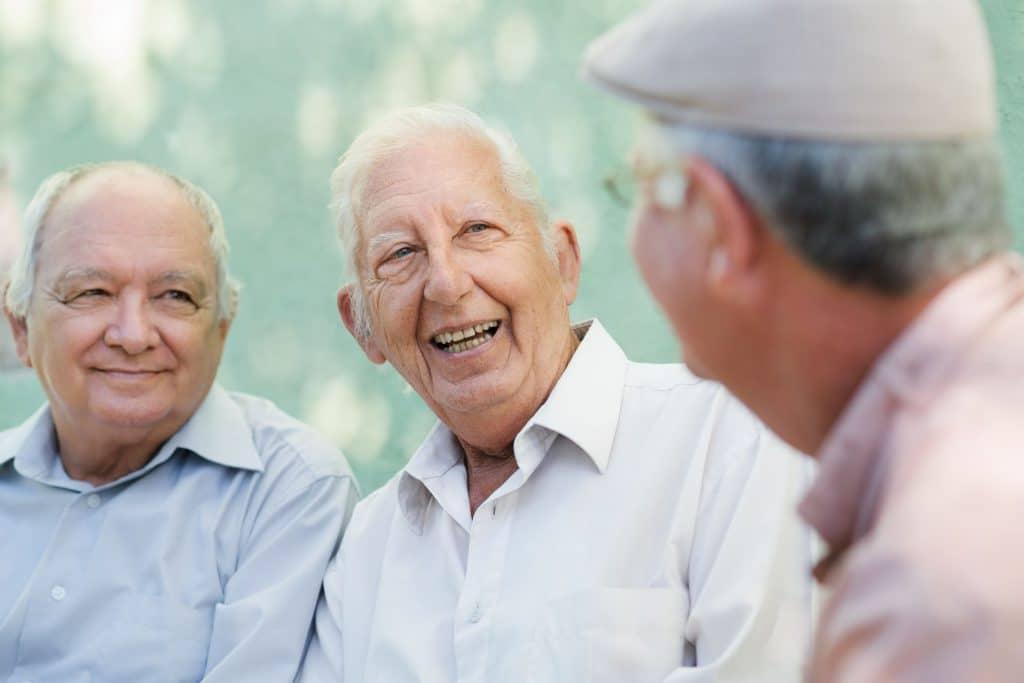grupo de três idosos do sexo masculino conversando e rindo no banco em parque público