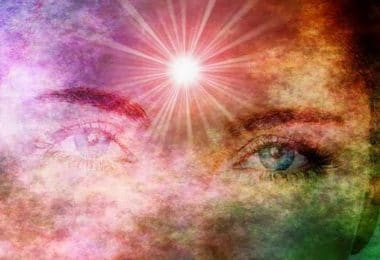 """Olhos de mulher esmaecidos por cores de arco íris. Há um forte ponto de luz um pouco acima do meio das sobrancelhas, na região esotericamente reconhecida como """"terceiro olho"""""""