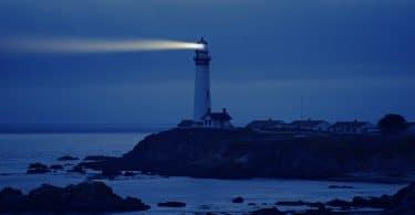 Farol emitindo luz para o mar durante a noite, auxiliando no caminho dos navegantes. Ele está sobre uma elevação de terra, bem como as casas ao redor.