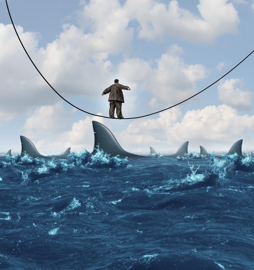 Homem se equilibrando sobre corda, que atravessa mar cheio de tubarões.