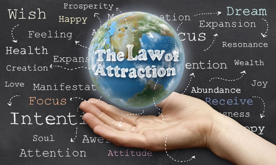 """Segurando o planeta Terra com a frase """"Lei da Atração"""" em inglês"""