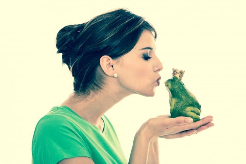 Mulher fazendo biquinho para beijar sapo com coroa em suas mãos