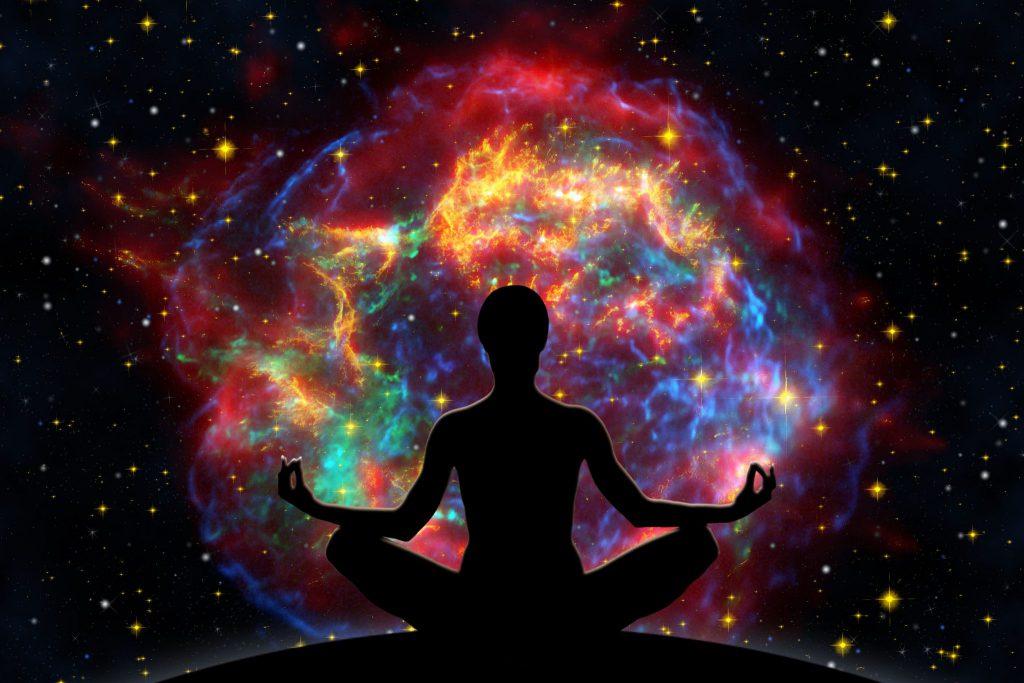 Ilustração de pessoa sentada em posição de meditação, com universo colorido.