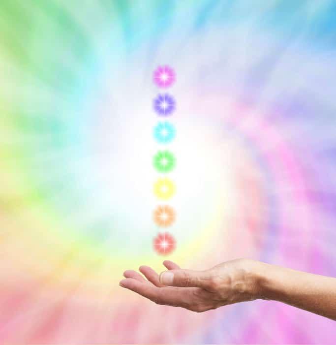 mão abaixo de uma fileira de círculos redondos iluminados cada qual com a cor de um chakra