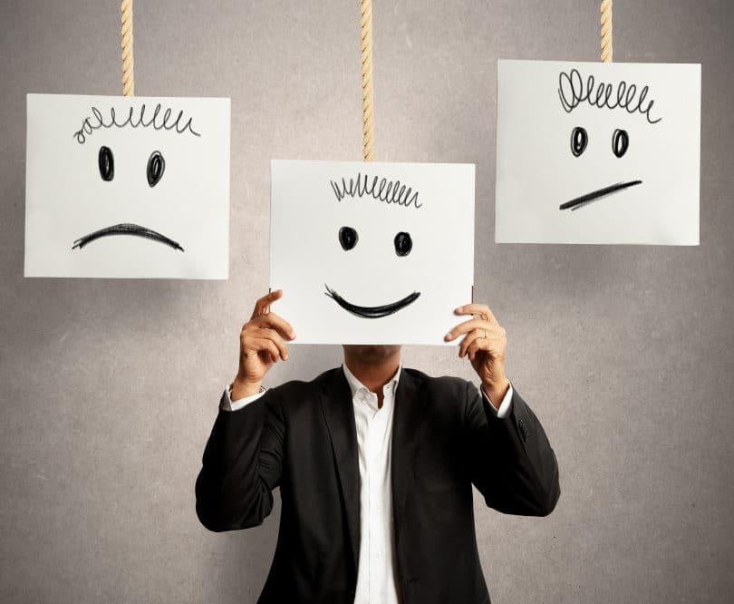 Homem escondendo o rosto em uma placa com um rosto feliz no meio de duas outras placas com rostos tristes e chateados.