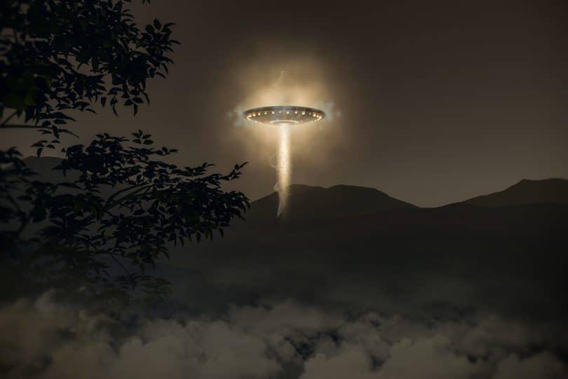 Nave extraterrestre sobrevoando paisagem escura a noite vista de longe