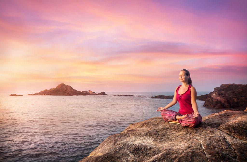 Mulher sentada em pedra, ao por do sol, meditando