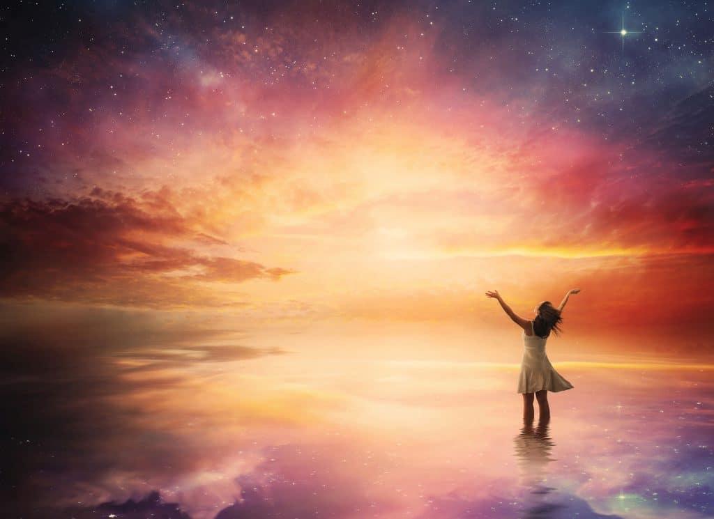 Mulher olhando para o universo em um final de tarde.