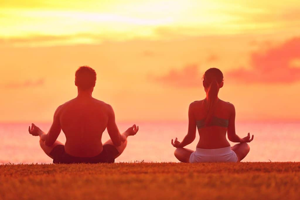 um casal sentado, meditando, de frente para o mar.