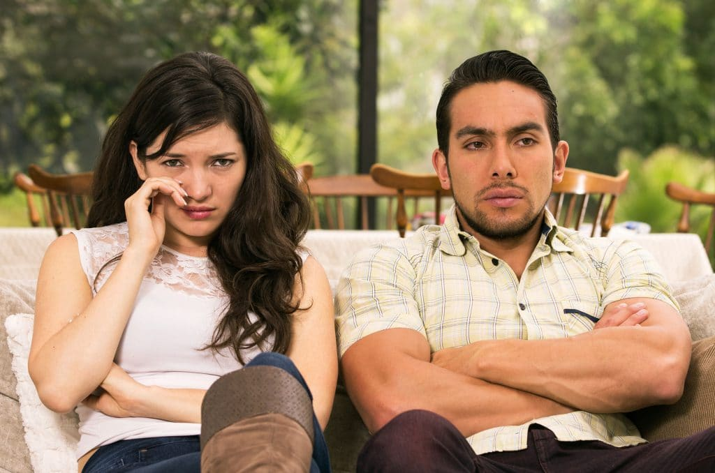 Casal brigado, sentados em um banco em um jardim, ambos emburrados e com cara de triste.