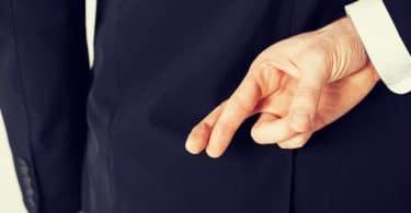 Homem de terno com a mão atrás das costas com os dedos cruzados em sinal de sorte.