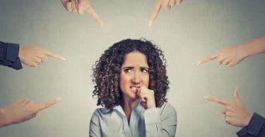 Mulher apreensiva, mordendo o dedo enquanto dedos apontam para a mesma