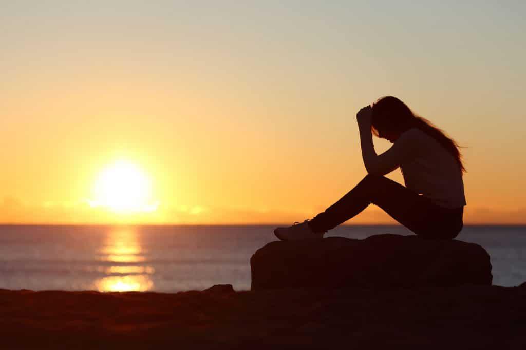 Silhueta de uma mulher sentada em uma praia com a cabeça apoiada nas mãos