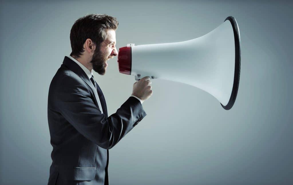 Homem vestido de social, gritando em uma megafone gigante
