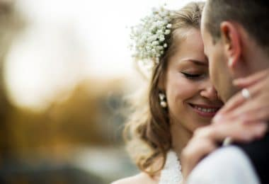 Casal se abraçando com os rostos próximos. Mulher sorri carinhosamente para o homem.
