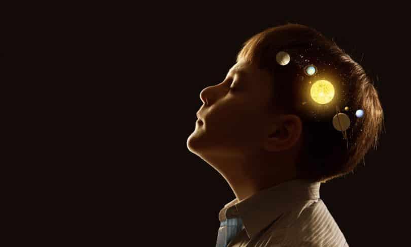 Menino visto de perfil, com os olhos fechados e planetas ilustrados em sua cabeça.
