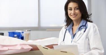 Médica sorrindo para a câmera enquanto segura as anotações de um paciente