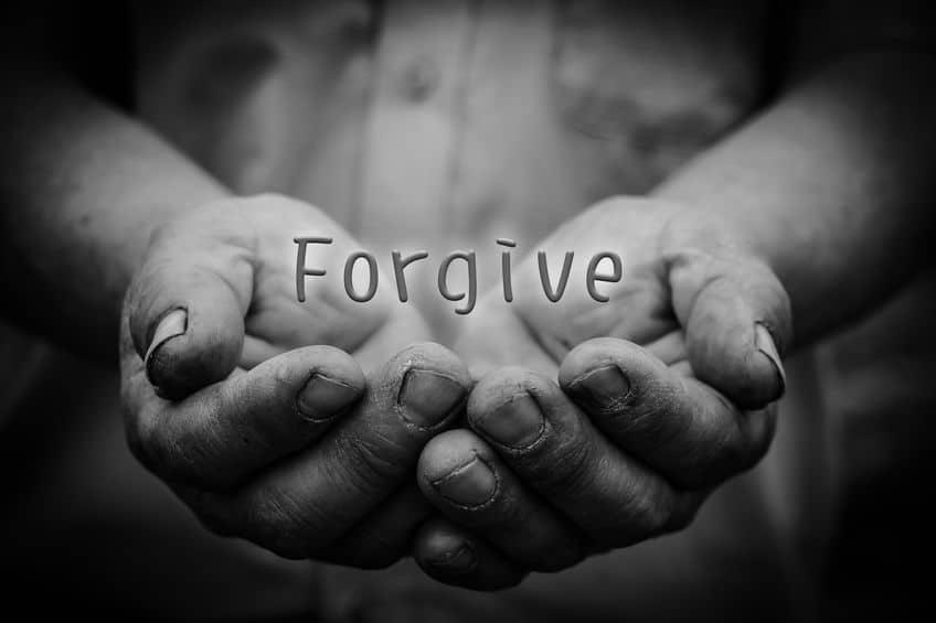 """Mãos segurando a palavra """"forgive"""", """"perdoar"""" em inglês"""