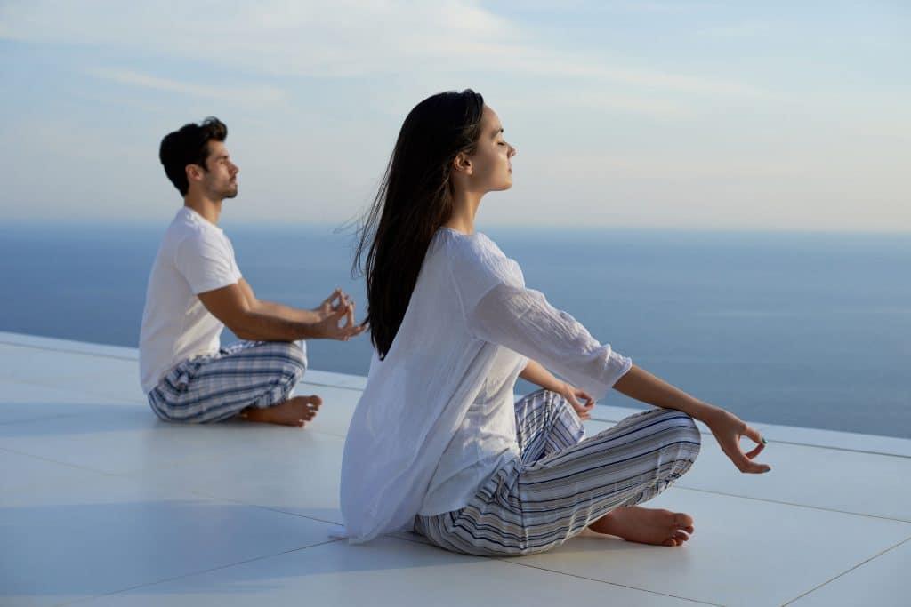 Casal sentado em um piso brando, meditando olhando para o horizonte