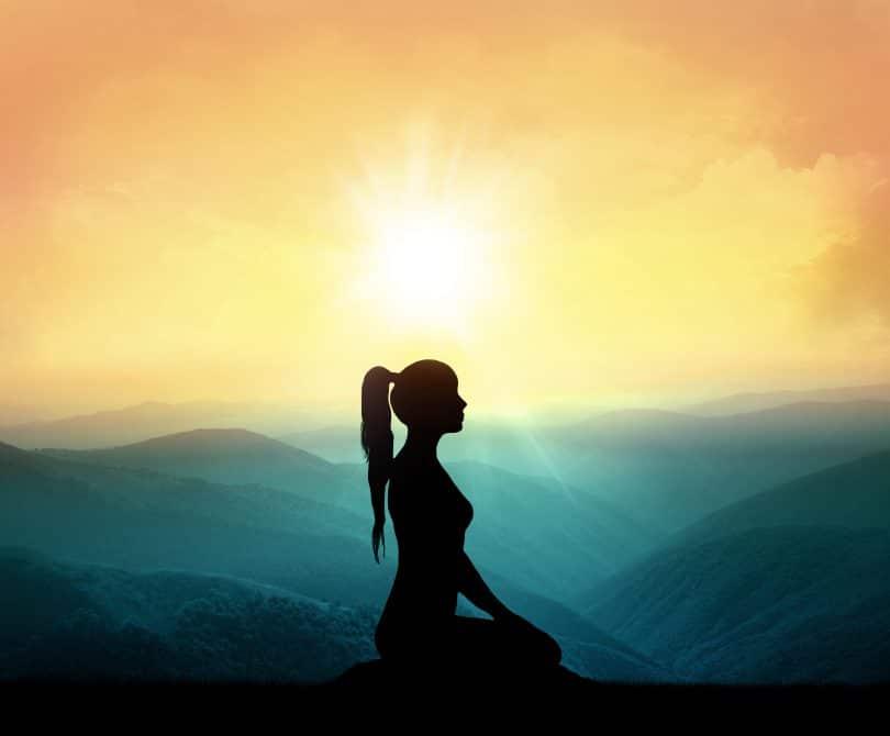 Silhueta de uma mulher de perfil sobre montanhas com o pôr do sol ao fundo.