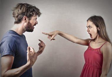 Homem e mulher discutindo. A mulher aponta o dedo para a cara do homem, enquanto este levanta os braços em sinal de irritação.