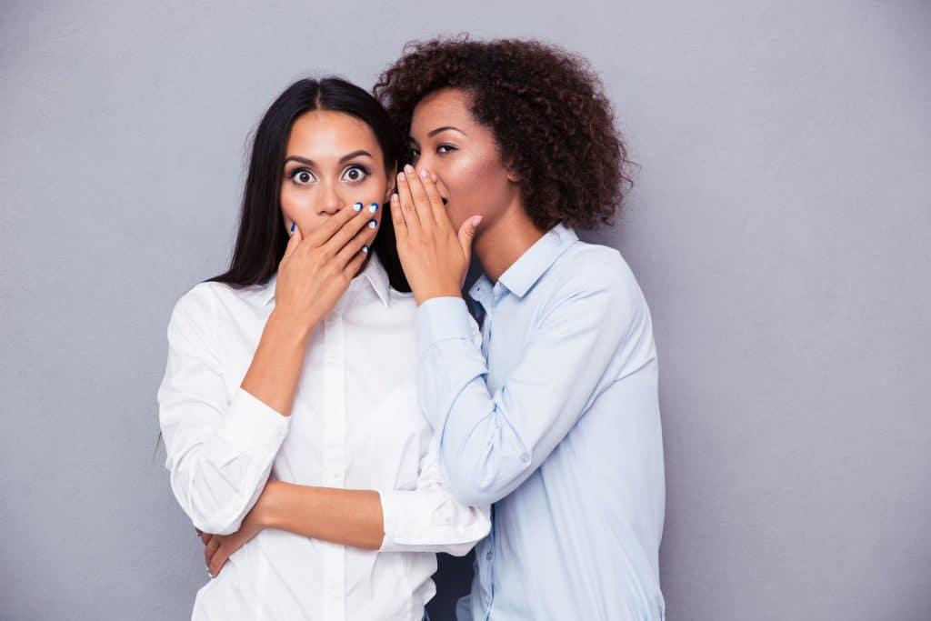 Duas mulheres negras, jovens, uma contando um segredo no ouvido da outra, que mostra surpresa.