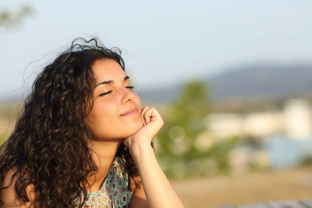 Mulher branca, jovem, sentada no chão, tomando sol no rosto, com os olhos fechados.