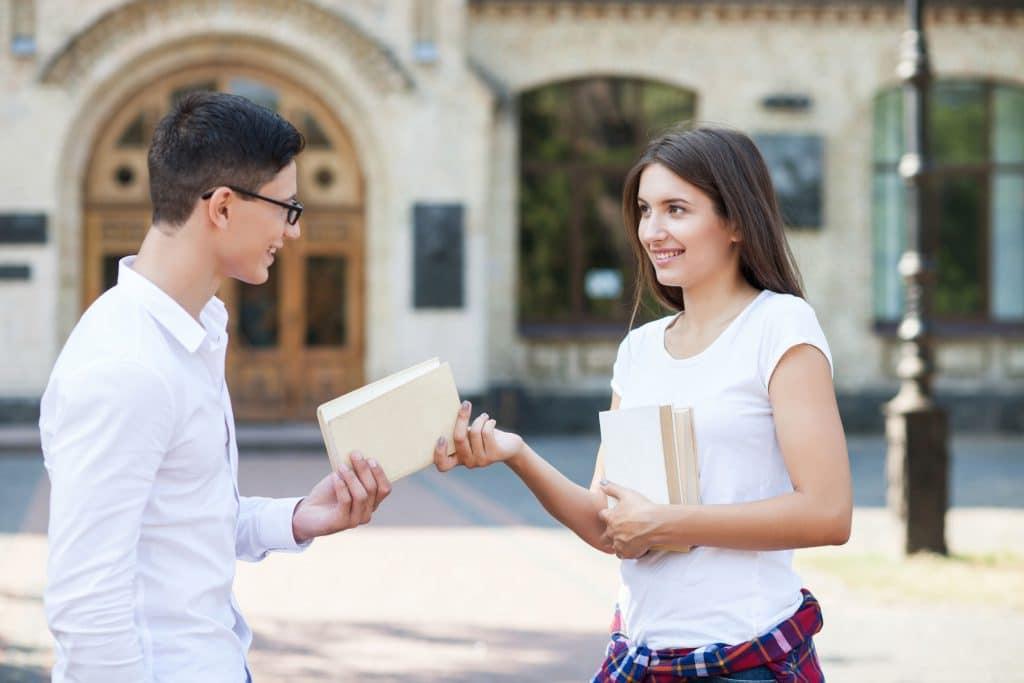 Mulher branca, jovem, entregando um livro para um homem branco e jovem